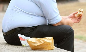 Obese man eats fast food